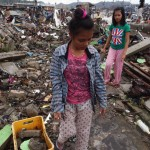 Two teenage girls help clear the rubble from their destroyed home